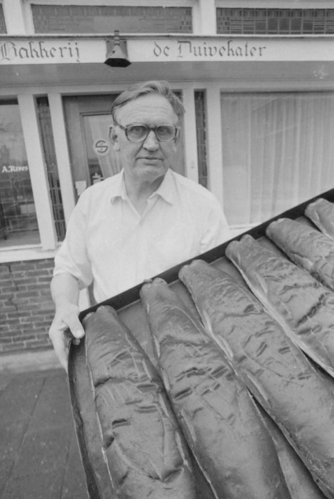 Anton Kroes met een bakplaat duivekaters, staand voor zijn bakkerij in Nieuwendam (1974).